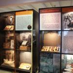 Beleuchtete Virtrinen mit Texttafeln und Objekten